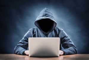 Shifty figure sitting at computer - hacking a website.